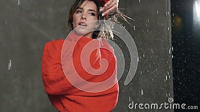 Le jeune danseur féminin professionnel exécute la danse acrobatique dans le studio sous la pluie de l'eau Folâtre la danse de fil banque de vidéos