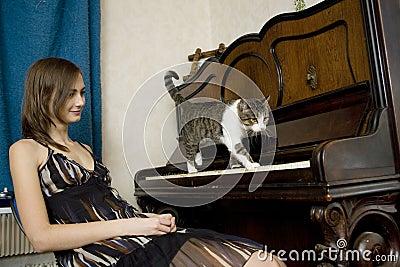 Le jeune femme observe le chat marcher sur le piano