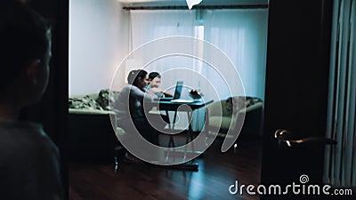 Le jeune garçon observe comme femme et homme à l'aide de l'ordinateur dans le salon, parle au papa clips vidéos