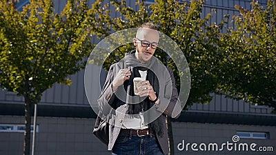 Le jeune homme d'affaires caucasien boit du café dans la ville centrale moderne outdoors Jeune marche barbue d'homme d'affaires banque de vidéos