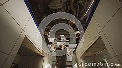 Le mécanicien déplace et prépare le support de service pour l'alignement des roues, station de voiture, réparation de suspension, clips vidéos
