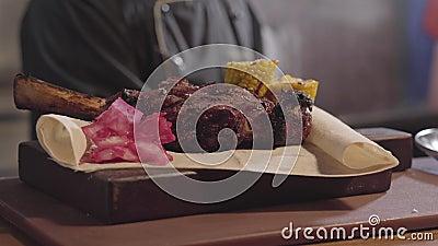Le mani del cuoco unico nei guanti neri del cuoco hanno messo il cavolo rosso ed i funghi con la carota vicino al pezzo cucinato  video d archivio