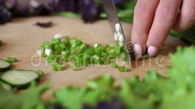 Le mani delle donne hanno tagliato le cipolle verdi su un tagliere rotondo di legno Primo piano video d archivio