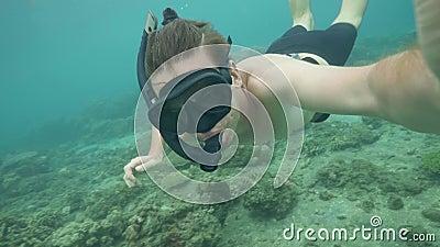 Le masque naviguant au schnorchel de soufflement de jeune homme pour égalisent la pression dans des oreilles tout en plongeant en clips vidéos