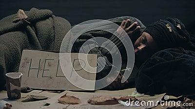 Le mendiant couché dans la rue avec de la bible, aidez à parler sur du carton, demandez de la charité clips vidéos