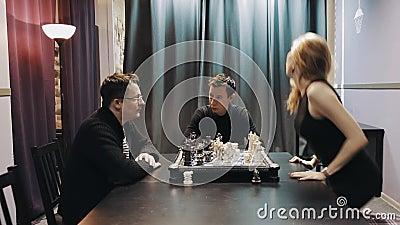 Le milieu a vieilli l'homme jouant des échecs avec la femme qui marche loin pendant qu'un autre homme marche dedans banque de vidéos