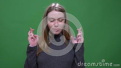 Le mod?le blond joyeux prie avec les doigts crois?s esp?rant la chance et le succ?s d'isolement sur le fond vert de chromakey banque de vidéos
