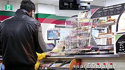 Le mouvement des personnes alignent pour payer la nourriture à la caisse de sortie 7 onze