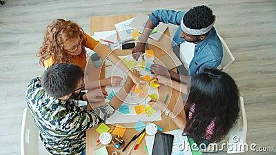 Le mouvement lent de collègues créatifs qui réalisent un collage en écrivant des idées au bureau clips vidéos
