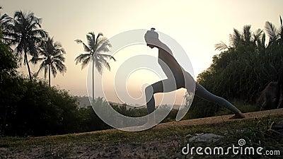 Le praticien de yoga fait le surya namaskar sur le mouvement lent de route banque de vidéos