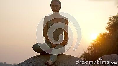 Le praticien de yoga met la jambe sur la hanche faisant le mouvement lent d'asana clips vidéos