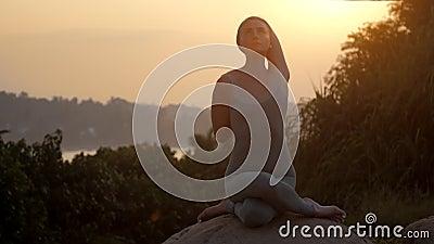 Le praticien de yoga s'assied dans le gomukhasana sur le mouvement lent de roche clips vidéos