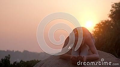 Le praticien fait l'exercice sur la roche au mouvement lent de hausse du soleil banque de vidéos