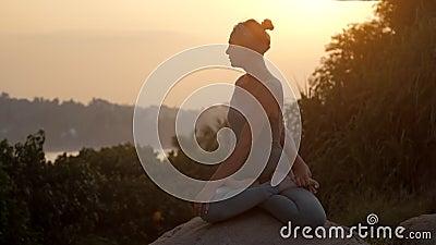 Le praticien s'assied dans la pose tournée de lotus sur le mouvement lent de roche banque de vidéos