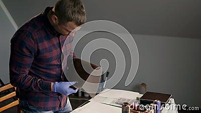 Le processus de la fabrication un portefeuille en cuir fait main Le maître examine un morceau de cuir peint handmade banque de vidéos
