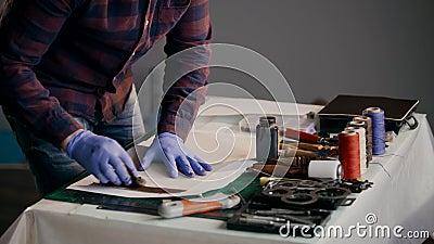 Le processus de la fabrication un portefeuille en cuir fait main Le maître peint un morceau de cuir dans le brun handmade clips vidéos