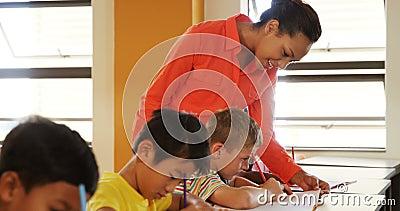 Le professeur aidant l'école badine avec leurs devoirs dans la salle de classe banque de vidéos