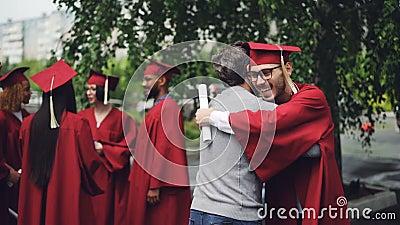 Le professeur d'université félicite son étudiant après la cérémonie l'étreignant et serrant la main, le professeur est fier clips vidéos