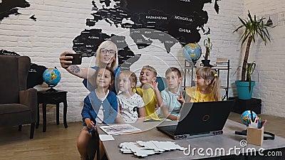 Le professeur féminin heureux avec des élèves sont se reposer du bureau et posent pour le selfie dans la classe de géographie à l banque de vidéos