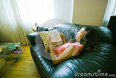 Le relevé de fille sur le sofa