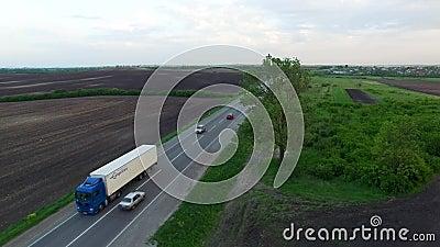 Le tir aérien du camion conduisant une route benween des champs clips vidéos