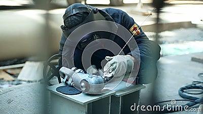 Le travailleur industriel avec des éléments d'inox de soudure de masque protecteur en structures métalliques fabriquent l'atelier banque de vidéos
