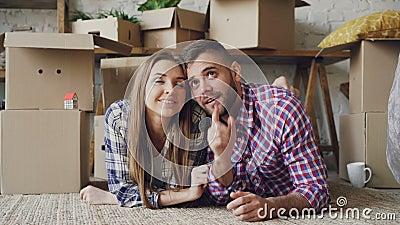 Le type barbu gai donne la clé à son amie et l'embrasse se trouvant sur le plancher du nouvel appartement Affection, les jeunes banque de vidéos