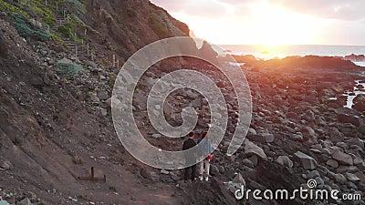 Le type et le support de fille sur l'océan au coucher du soleil, au pied des falaises, plage de Benijo, Ténérife, Îles Canaries banque de vidéos