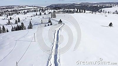 Le vol au-dessus de la neige a couvert la route dans les montagnes Film aérien du bourdon 4k banque de vidéos