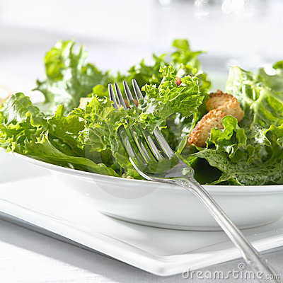 Leafy green salad with croutons and fork