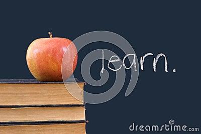 Learn written on blackboard with apple and books