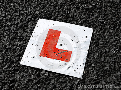 Learner drivers plate against black tarmac