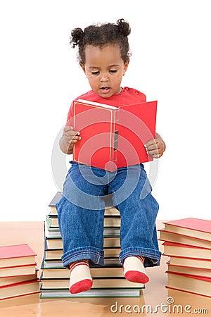 Lectura del bebé que se sienta en una pila de libros
