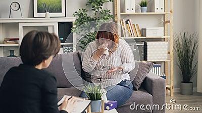 Ledsen flicka med äta oordning som gråter i terapeuts kontor som rymmer papperssilkespappret arkivfilmer