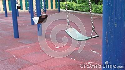 Leere Kettenschwingungen auf dem modernen Kinderspielplatz in der Stadt. Sonniger Tag stock video