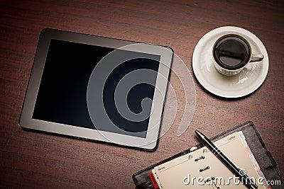 Lege tablet en een kop van koffie in bureau