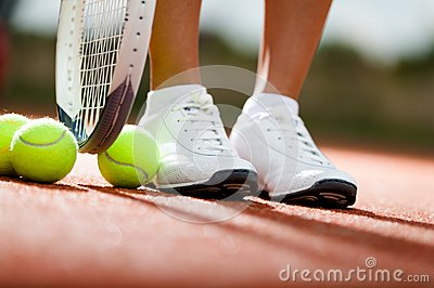 Legs of athlete near the tennis racket