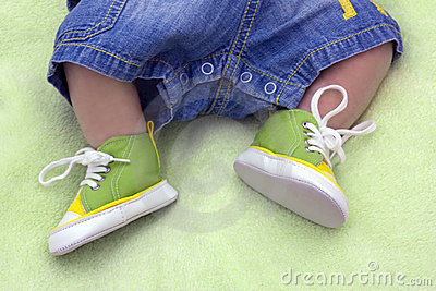Legs of the child in gym shoes on a green blanket