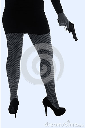 Legs of dangerous woman with handgun and black shoes silhouette