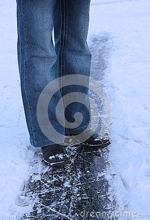 Winter background - legs of girl on the ice