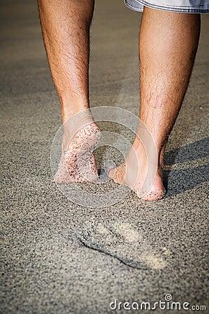 Legs of a man walking on the beach