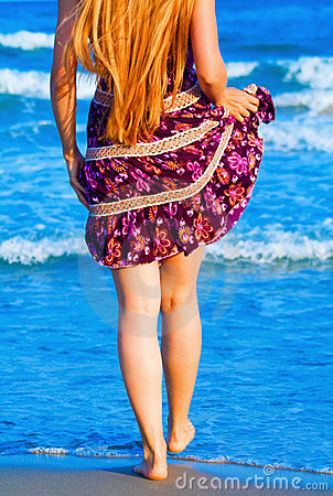 Legs of sexy woman walking into the sea