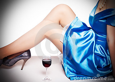 Legs in shoes  and a glass of red wi