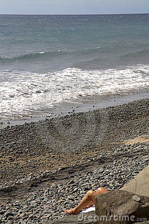 Legs of sunbather on beach