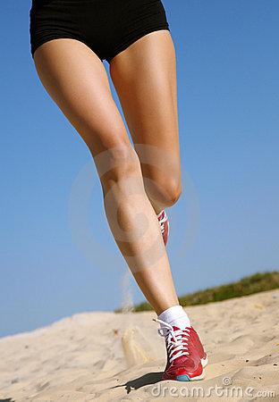 Legs of woman running on sand