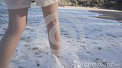Leinwände asiatischer Mädels, die am Strand spazieren gehen, mit Wellen, die an einem Meeresufer brechen stock video