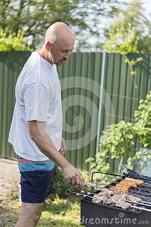 Free Leisure, Food, People And Holidays Concept - Happy Young Man Cooking Meat On Barbecue Grill At Outdoor Summer Party Royalty Free Stock Photography - 116082357