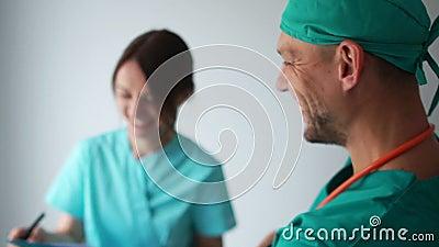 Lekarze, mężczyzna i kobieta rozmawiają i śmieją się w korytarzu kliniki Personel medyczny w wolnym czasie zdjęcie wideo