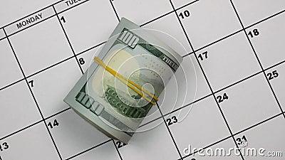 Lembrete de papel do calendário sobre pagar impostos A mão põe dólares ao lado dos impostos da palavra video estoque