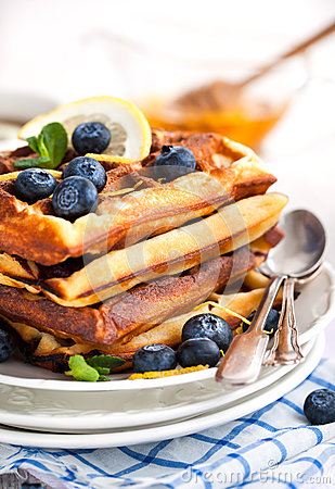Lemon blueberry waffles with honey, zest, fresh berries and cup of tea ...